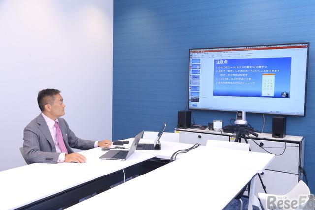 会社の会議室エリアで、常設のスクリーンと、ノートパソコン、iPadを用いて講義を行う粟国氏